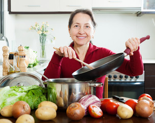 mature woman cooking lunch  with skillet