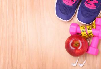 Sport equipment. Sneakers, dumbbells, measuring tape, apple