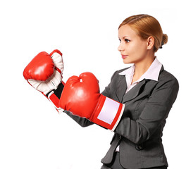 Business woman wearing boxing gloves punching isolated
