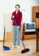 happy mature housewife cleaning at home