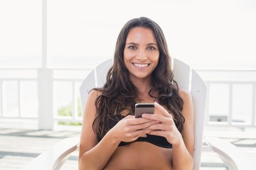 brunette sitting on a chair and texting with her mobile phone