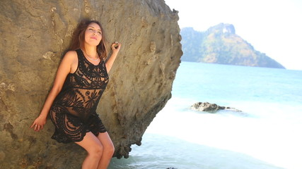 young european brunette girl poses by rock on sea coast