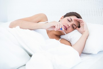 Sick woman looking at her thermometer