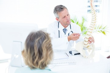 Doctor showing spine model to his patient