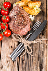Grilled steaks on wooden table