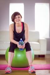 Fit woman with bottle on exercise ball