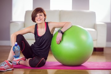 Fit woman sitting next to exercise ball