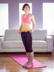 Portrait of happy slim woman measuring waist