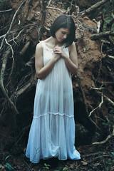 Beautiful woman praying among dead trees