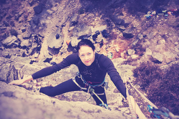 Happy young woman climbing wall.