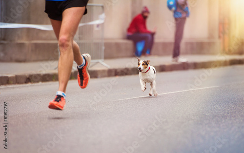 Leinwanddruck Bild Unrecognizable young runner and a dog at the city race