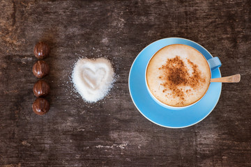 Cup of coffee and a heap of sugar on a wooden table background