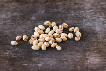 Heap of pistachio nuts, close up on wooden table background