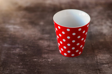 Empty red polka dot cup on a wooden table background