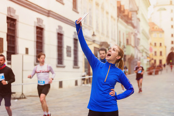 Beautiful young woman in the city race taking a selfie
