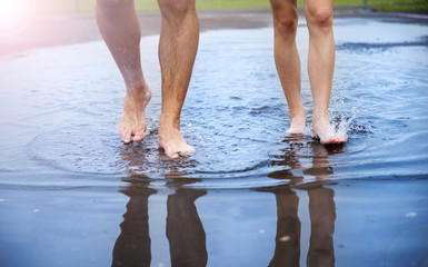Unrecognizable woman and man in barefoot in a puddle