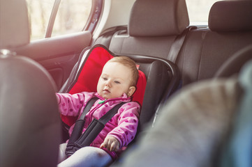 Mother in a car, having her little baby girl in a child seat