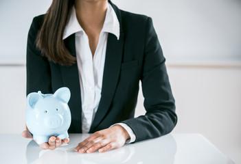 Conceptual Businesswoman Holding a Piggy Bank