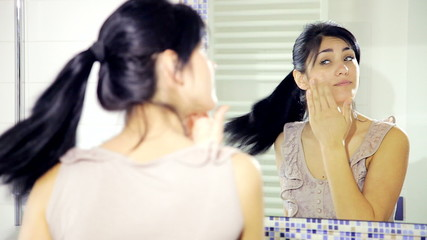 Woman in front of mirror putting makeup medium shot