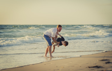 father playing on beach with little son laughing excited