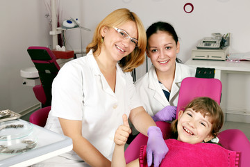 little girl patient with thumb up in dental office