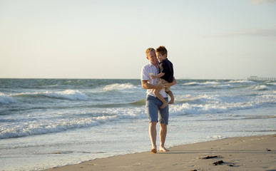 young happy father holding little son walking on beach