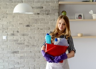 Smiling  blond woman holding a bucket full of cleaners