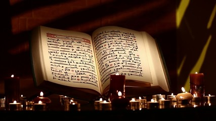 Old rare Quran with candles
