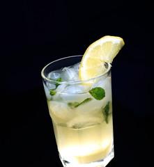Glass of lemonade with the slice of lemon and mint. Dark backgro