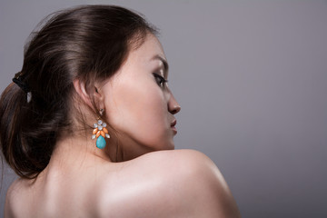 Close-up portrait of a girl with bare shoulders in profile