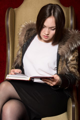 Young girl in a fur coat sitting chair and reading a book