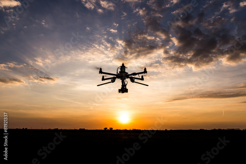 Leinwandbild Motiv Professional drone flying in the sunset
