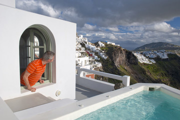 Man is looking Santorini crater from the window