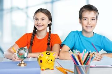 School. Portrait of happy school children drawing with crayons
