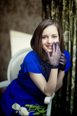 Smiling girl in blue dress and lace gloves