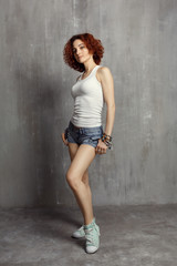 girl in a vest and sneakers standing on a gray background textur