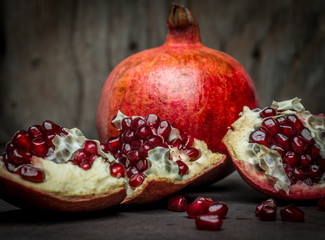 Some red juicy pomegranate, whole and broken