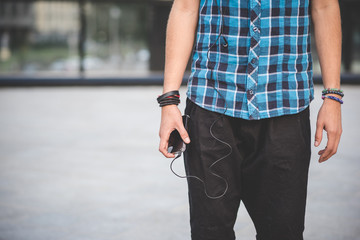 close up of hand guy with smartphone and earphones