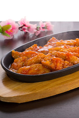 Sweet and sour chicken on a stone plate over wooden background