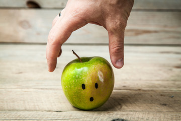 hands reaching for a green apple on wooden background