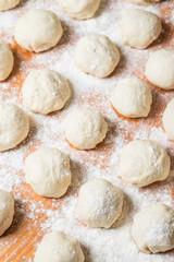 Small balls of fresh homemade dough on floured wooden board