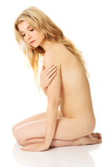 Young nude woman sitting on knees