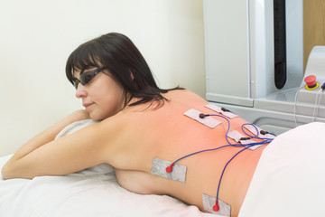 woman in massage clinic makes electropulse