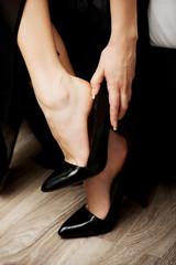 Woman putting on high heels.