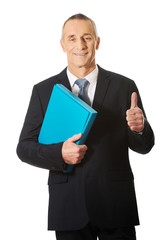 Businessman with ok sign holding a binder