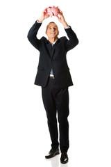Happy businessman holding piggybank