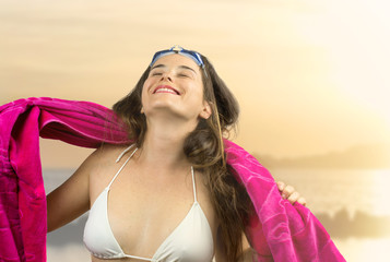 relaxed girl in beachwear with swimming goggles  against beach a