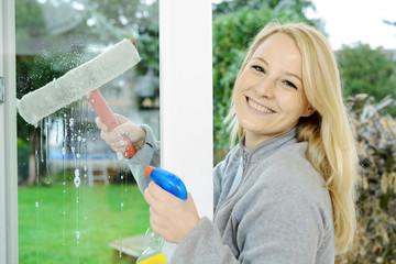 Frau wischt Fenster streifenfrei mit Wischer