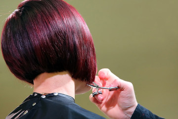 Hairdresser trimming red hair with scissors