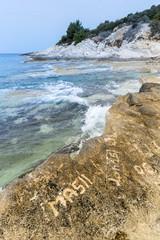 Inschrift auf Felsen an der Küste